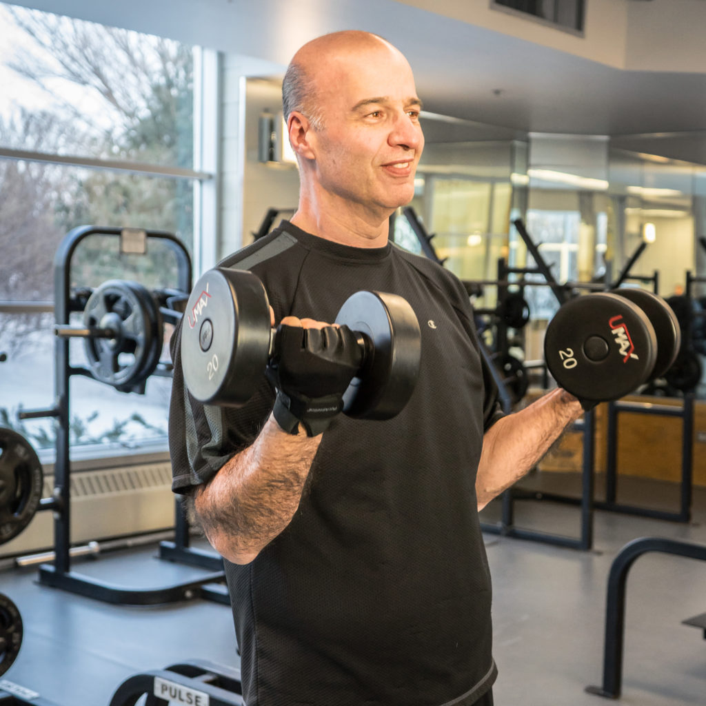 Paul Benito, member,  lifting weights at the Wellness Institute as part of his commitment to a preventative, healthy lifestyle.